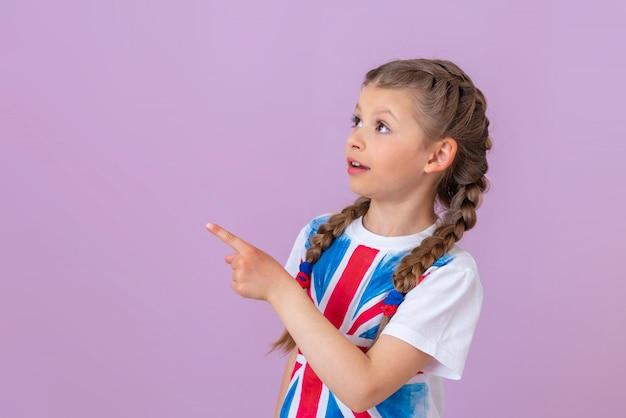 Маленькая девочка с косичками и изображением английского флага на футболке показывает пальцем в сторону.