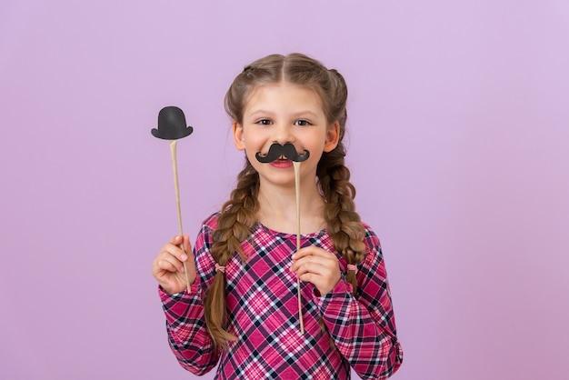 땋은 머리를 한 어린 소녀는 한 손에는 멋진 콧수염을, 다른 손에는 모자를 들고 있습니다.