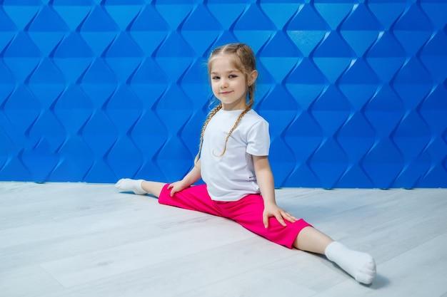 Маленькая девочка с косичками в белой футболке на синем фоне сидит в шпагате на полу и улыбается. детские эмоции занятие спотром, веселье