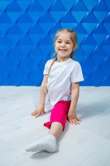 파란색 배경에 흰색 티셔츠를 입은 땋은 머리를 한 어린 소녀가 바닥에 꼬기에 앉아 미소를 짓고 있습니다. 아이들의 감정 직업 스포트롬, 재미