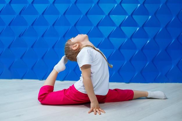 青い背景に白いtシャツを着たおさげ髪の少女が床にひもで座って微笑んでいます。子供の感情の職業spotrom、楽しい