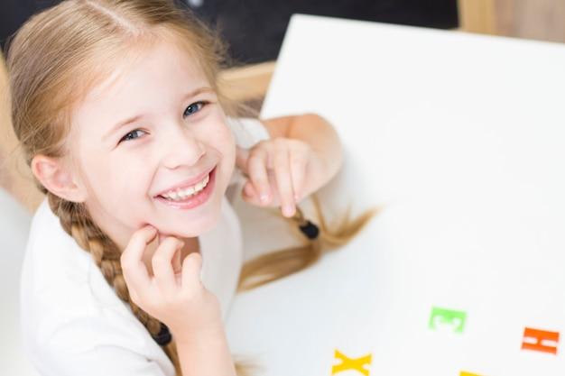 땋은 머리를 가진 어린 소녀가 웃고 있고 책상에 앉아 있습니다. 학교로 돌아가다. 가정교육