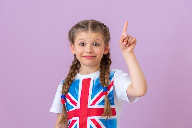 Маленькая девочка с косичками показывает пальцем вверх.
