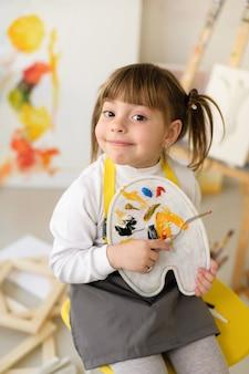 ホーム スタジオ ワーク ショップでポニーテールの少女は、塗料とパレット ナイフでパレットを保持します。
