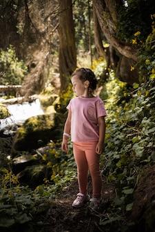 ポニーテールの少女が森の中に立って目をそらしている