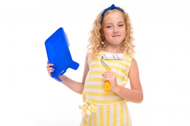 Маленькая девочка с рыжими ворсистыми волосами в бело-желтом полосатом летнем костюме с голубой повязкой на голове с помощью валика для росписи стен.