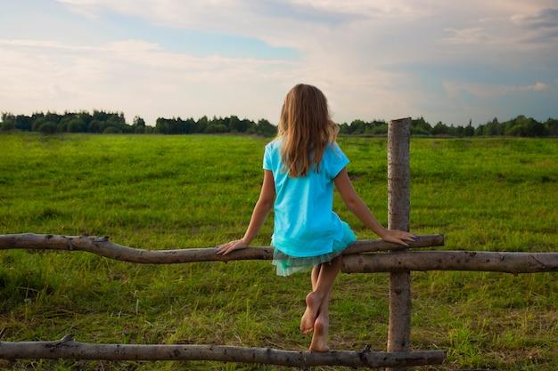 夏の牧草地の木製の柵に靴のない少女が座っている