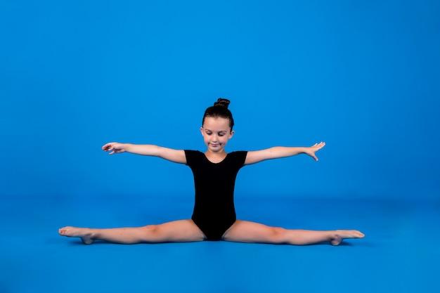 Маленькая гимнастка в черном купальнике делает шпагат на синем фоне с местом для текста