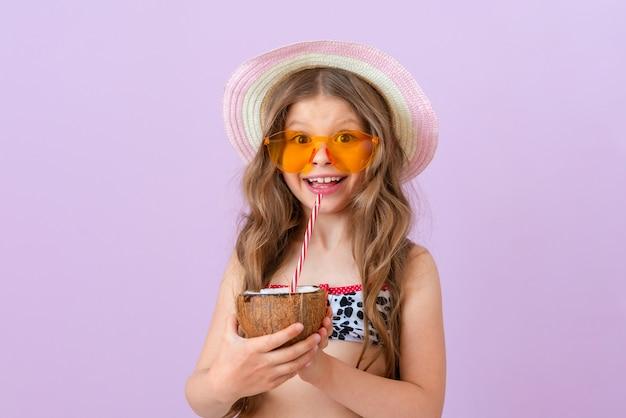 작은 행복한 소녀는 코코넛으로 만든 맛있는 여름 칵테일을 마신다. 격리 된 배경입니다.