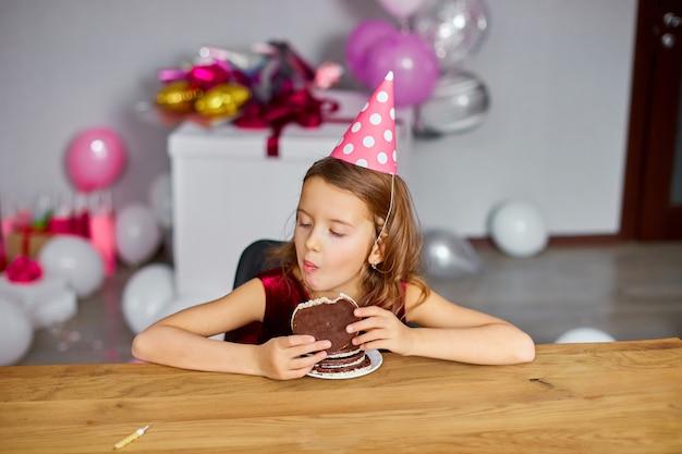 Маленькая счастливая девочка в шляпе на день рождения и ест праздничный торт