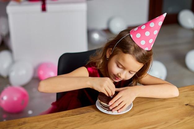 Маленькая счастливая девочка носит шляпу на день рождения вкусную свечу от именинного торта, корчит рожи, концепция вечеринки.