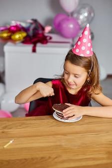 Маленькая счастливая девочка носит шляпу на день рождения вкусную свечу от именинного торта, корчит рожи
