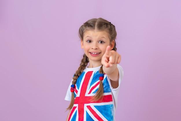Маленькая счастливая девочка с косичками и изображением английского флага на футболке указывает пальцем вперед.
