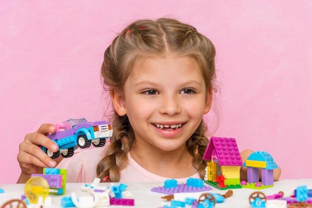 小さな楽しい女の子がキューブからカラーコンストラクターを収集します。