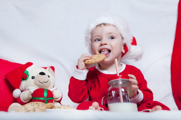 赤い帽子をかぶった小さな子供は、クッキーとミルクを食べます。赤い帽子の赤ちゃんのクリスマス写真。年末年始とクリスマス