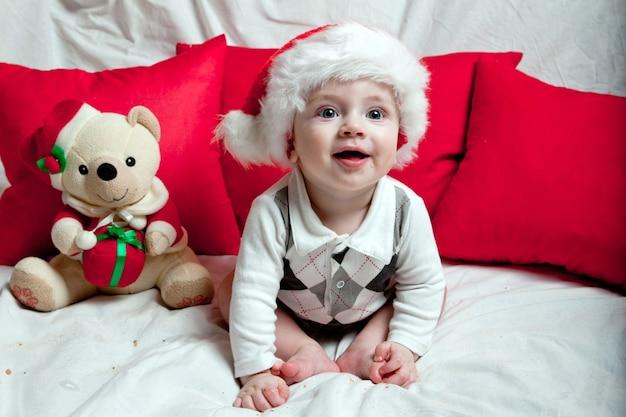 Маленький ребенок в красной шапочке ест печенье и молоко. новогодние праздники и рождество.
