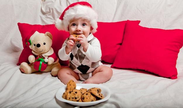 赤いサンタの帽子をかぶった小さな子供がクッキーと牛乳を食べます。赤いサンタの帽子をかぶった赤ちゃんのクリスマスポートレイト。