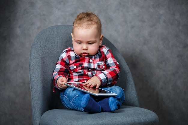 Маленький ребенок в рубашке играет с планшетом