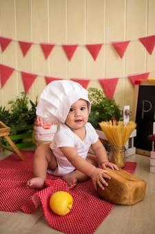 Маленький ребенок в белой поварской шляпе держит хлеб