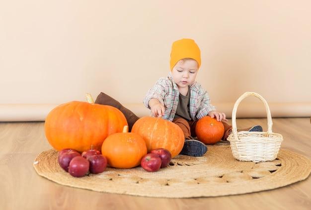 家のカボチャの中に小さな子供が座っています。秋のコンセプト