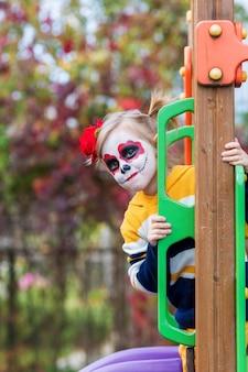 Painted face를 가진 어린 유치원 소녀는 놀이터에서 미끄럼틀을 타고 할로윈이나 멕시코 죽음의 날을 축하합니다.