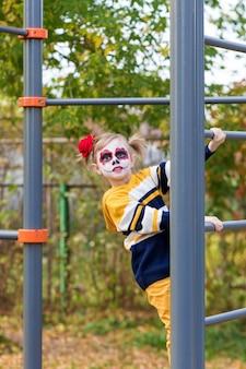 Painted face를 가진 어린 유치원 소녀가 놀이터의 스웨덴 벽에 올라 할로윈이나 멕시코 죽음의 날을 축하합니다.
