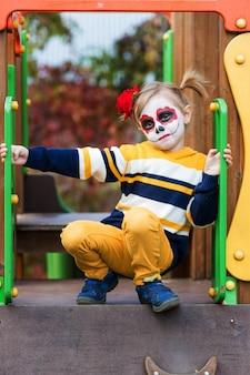 Painted face를 가진 유치원 소녀가 놀이터에서 미끄럼틀을 타고 할로윈이나 멕시코 죽음의 날을 축하합니다.