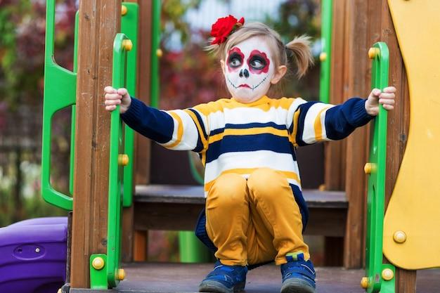 Painted face를 가진 유치원 소녀는 놀이터에서 재미있는 얼굴을 보여주고 할로윈이나 멕시코의 죽음의 날을 축하합니다.