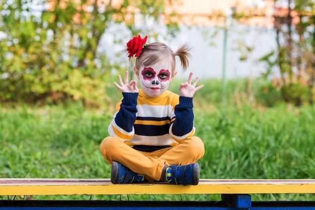 놀이터에서 로터스 위치에 벤치에 앉아 painted face를 가진 유치원 소녀가 할로윈이나 멕시코 죽음의 날을 축하합니다.