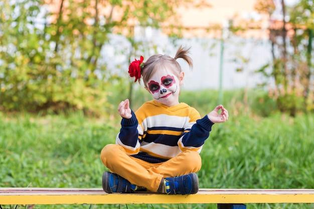 Painted face를 가진 유치원 소녀가 놀이터에서 웃고 할로윈이나 멕시코의 죽음의 날을 축하합니다.