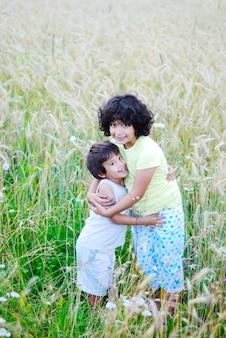 녹색 medow에 작은 예쁜 여자와 소년