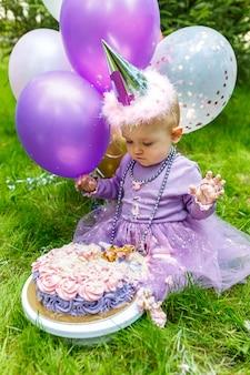 Маленькая хорошенькая девочка смешно портит свой первый торт в парке