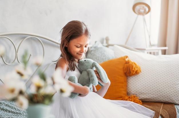 아름다운 하얀 드레스를 입은 예쁜 소녀가 장난감 토끼와 함께 밝은 방에서 침대에 앉아 있습니다.