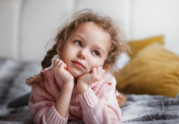 Маленькая хорошенькая девочка лежит на кровати и мечтает