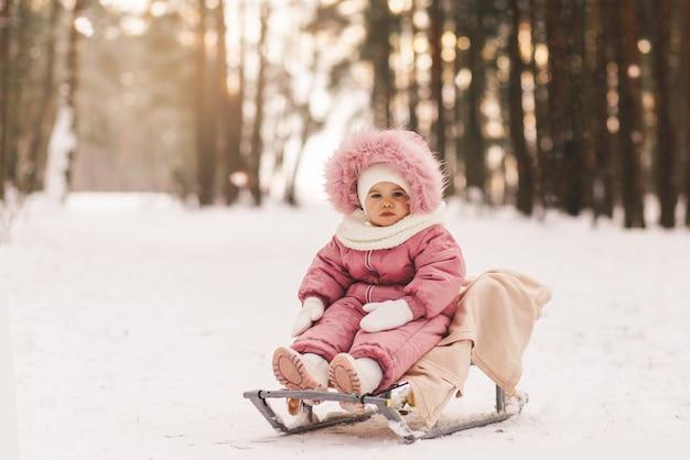 Маленькая симпатичная девочка на санках в заснеженном лесу зимой
