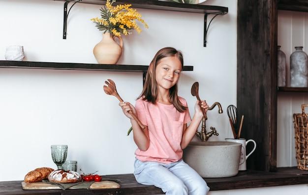 Маленькая симпатичная девочка играет на кухне со столовыми приборами.
