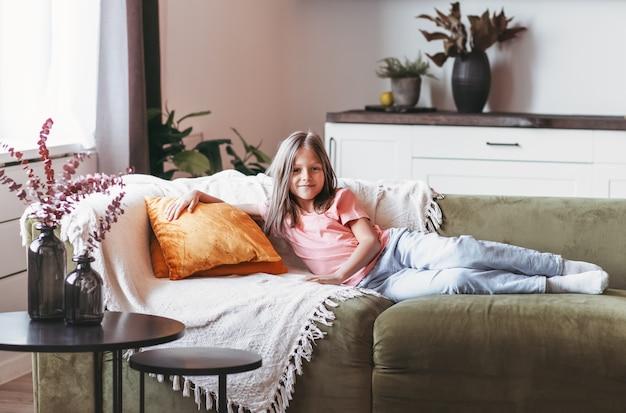 Маленькая симпатичная девочка отдыхает на диване в светлой комнате.