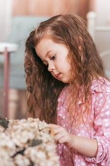 フォーニックヘアの小さなかわいい女の子が花を見ています。縦長のポートレート
