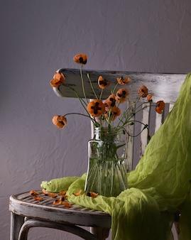ガラスの花瓶にポピーのクラシックなスタイルのスティリフに配置された小さな赤いポピーの花束