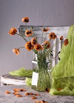 クラシックなスタイルでアレンジされた小さな赤いポピーの花束ヴィンテージの椅子にガラスの花瓶にポピーのスティリフ