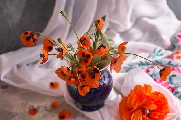 青いセラミック花瓶の小さな赤いポピーの花束