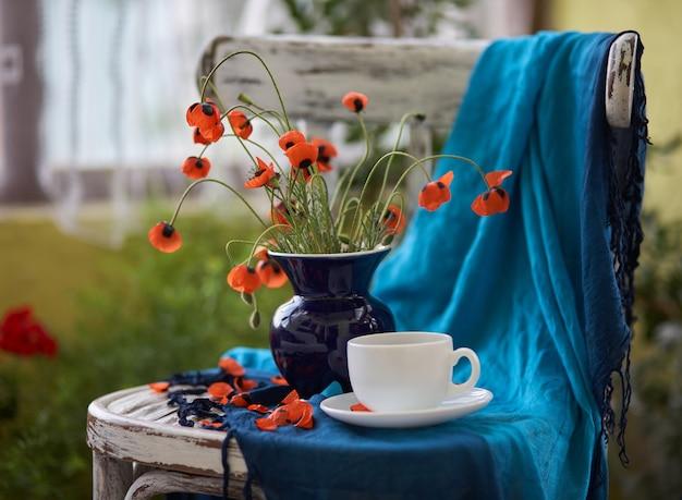 빈티지의 자에 파란색 꽃병에 작은 빨간 양 귀 비 꽃다발. 양귀비와 커피 한잔.