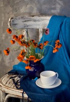 ヴィンテージの椅子に青い花瓶の小さな赤いポピーの花束。