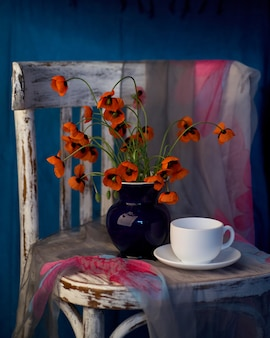 ヴィンテージの椅子に青い花瓶の小さな赤いポピーの花束