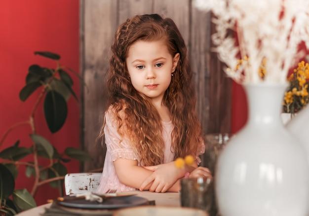 小さな悲しい女の子が台所のテーブルに座っています。昼食を待っています