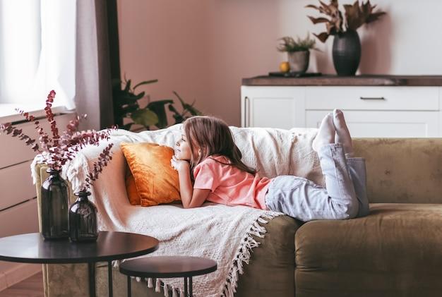 Маленькая девочка школьного возраста лежит на диване в светлой комнате и смотрит в окно. детские мечты