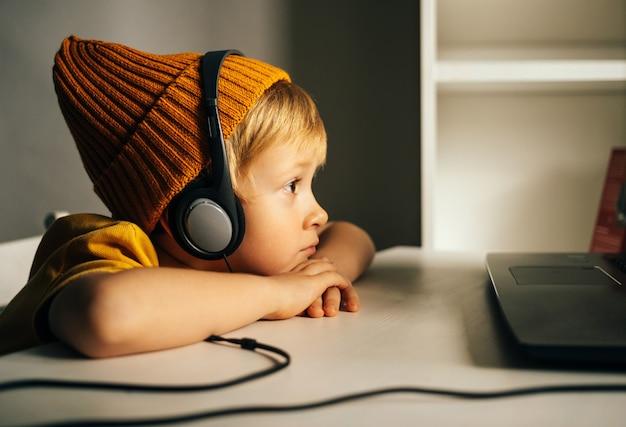 노란 모자를 쓴 작은 남학생이 집 테이블에 앉아 비디오 똥을 주의 깊게 보고 있다