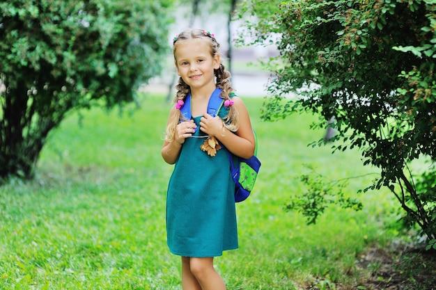 Маленькая школьница в зеленом платье со школьной сумкой в руках улыбается на фоне зелени в парке. снова в школу, образование, день знаний