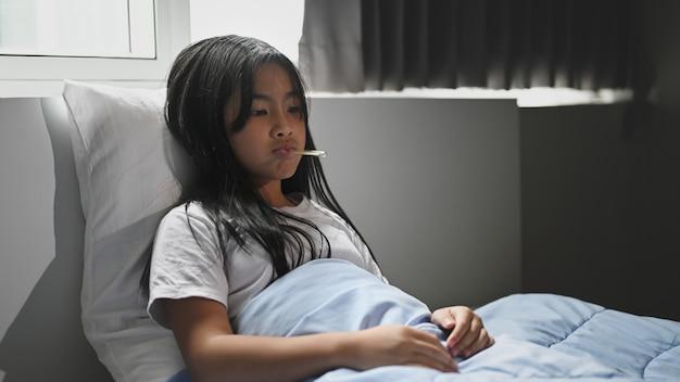 Маленькая больная девочка в одеяле лежит на кровати и измеряет температуру.