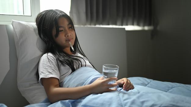 담요로 덮인 아픈 소녀는 침대에 누워 온도를 측정합니다.